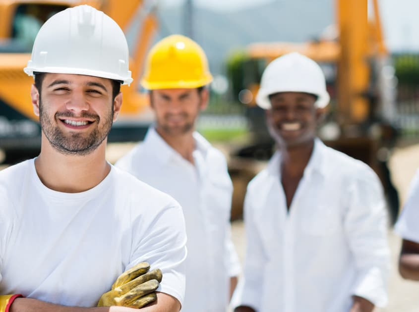 A diverse team of smiling construction men wearing hard hats