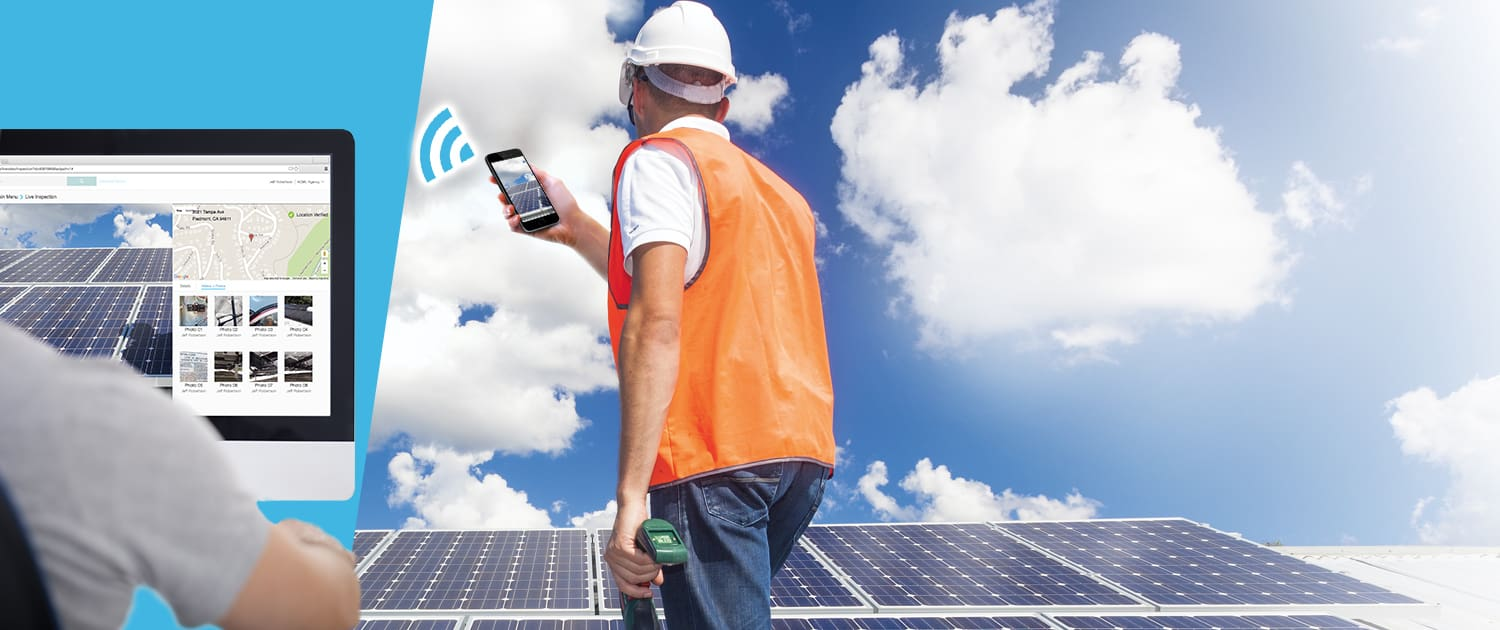 Construction worker standing on a roof with solar panels in a mostly sunny blue sky staring at his mobile phone with a photo of the solar array sending the photo to an inspector seated at a computer far away